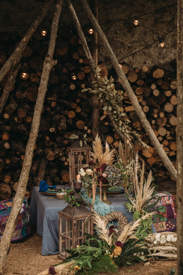 teepee made from old tall logs over low gypsy wedding table with cushions for chairs
