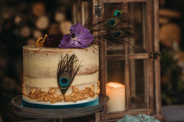 naked rustic wedding cake decorated with peacock feathers and a purple orchid