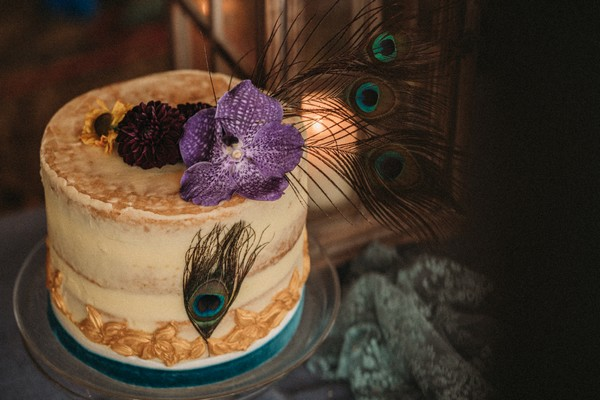 rustic wedding cake with peacock feathers and purple orchid