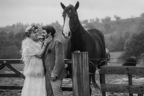 bride and groom stand next to shire horse in field
