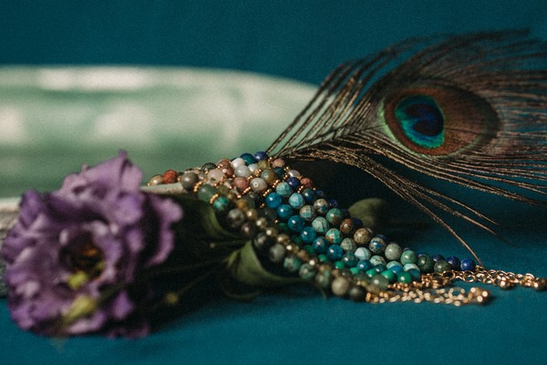 peacock feather, green beads and purple lisianthus flower on peacock blue fabric