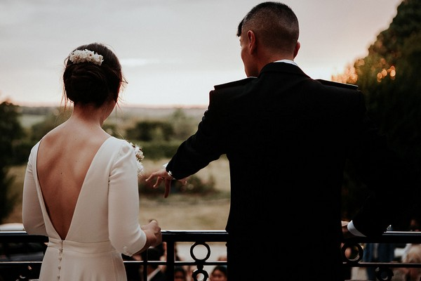 bride and groom overlook the grounds of chateau santeny on the balcony