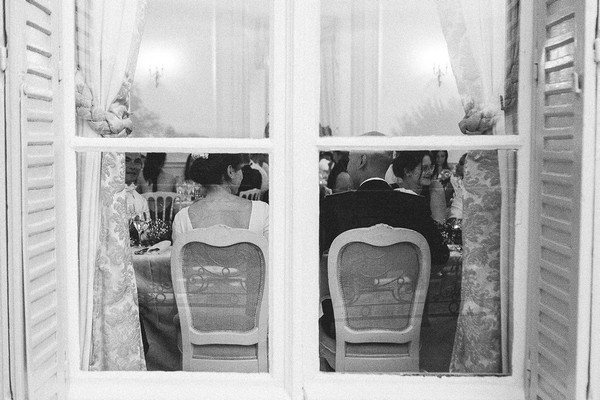 the back of the bride and groom at the wedding table through french windows