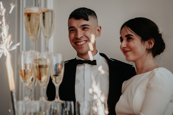 bride and groom smile behind tower of champagne glasses