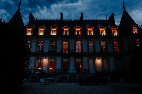 Chateau Santeny at night with lights on inside