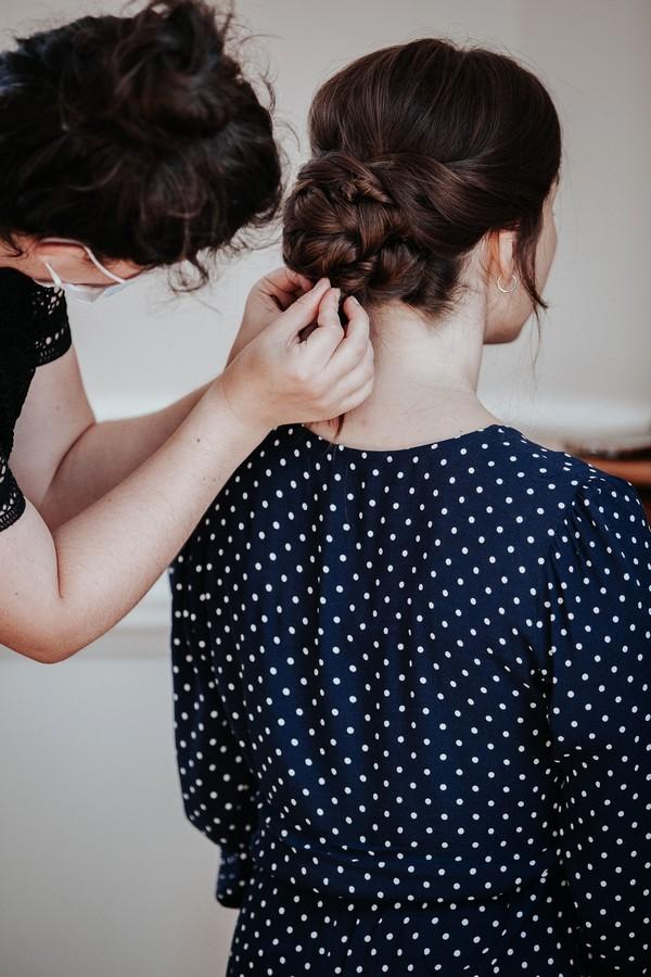 Bride in navy polka dot dress having hair styled for wedding