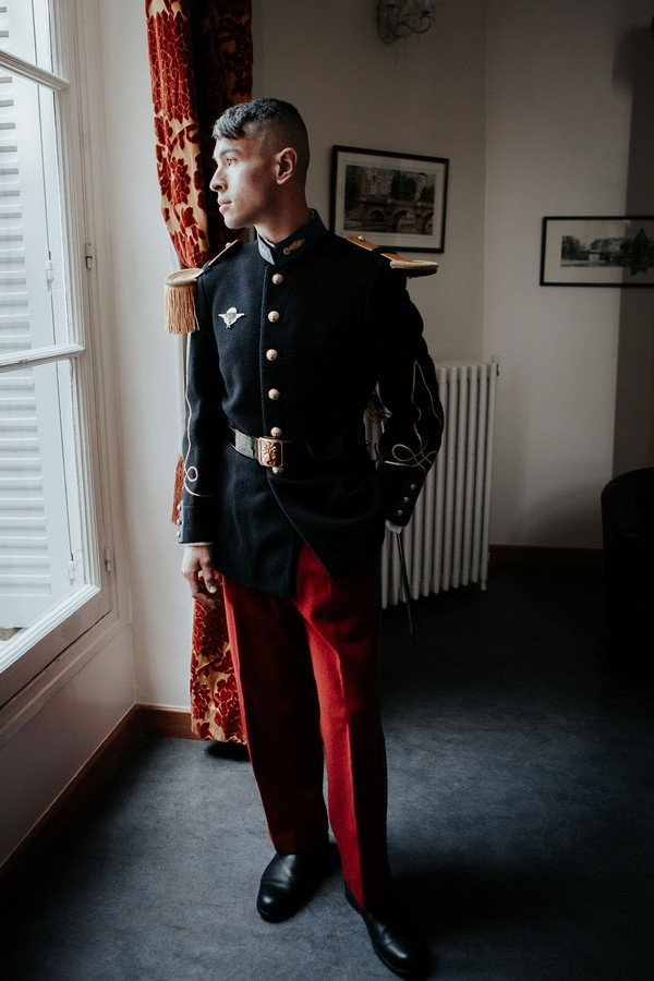 Groom in military uniform looks out french windows
