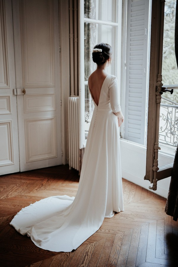 bride looks out french windows in white low back retro wedding dress