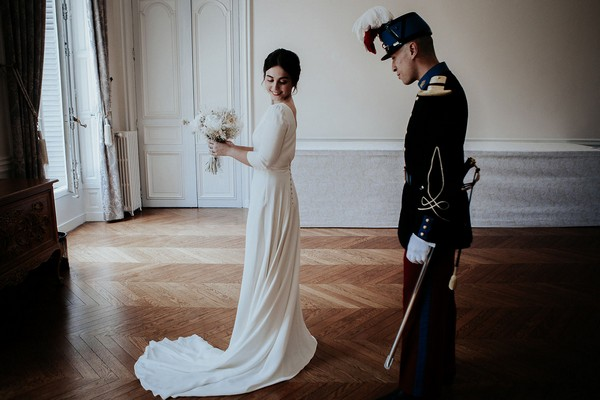bride in retro dress and groom in full military uniform meet in french chateau