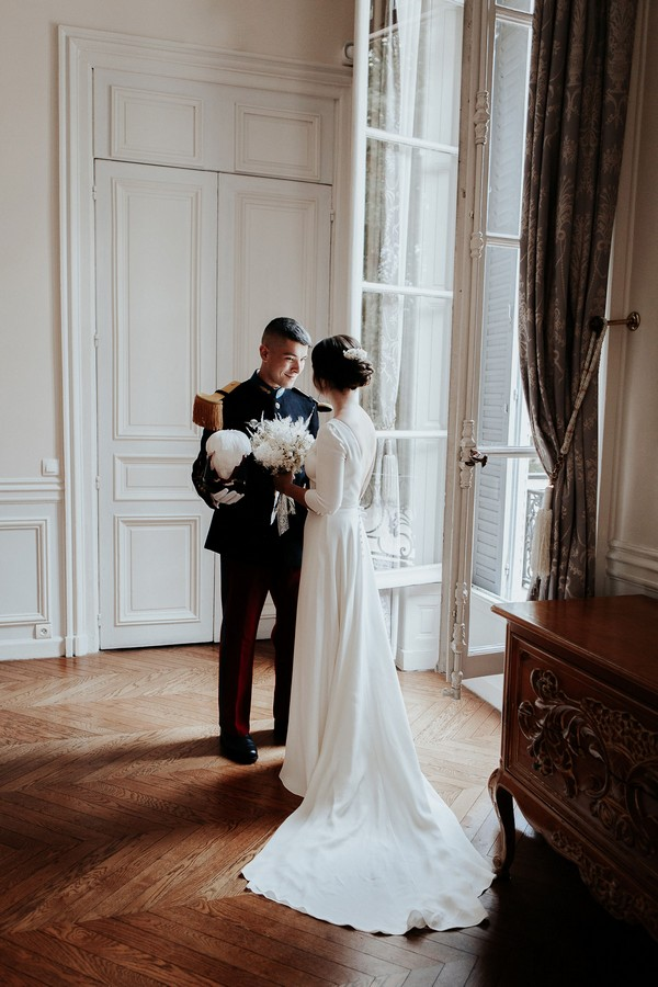bride in retro low back wedding dress meets her groom in full military uniform at the window of a french chateau