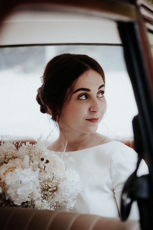 Bride looks out the window of a red vintage wedding car