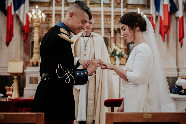groom places ring on brides finger under watch of the priest