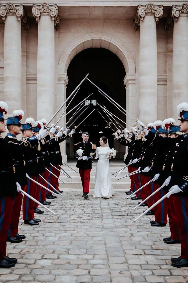 bride and groom walk out of the church through a saber arch