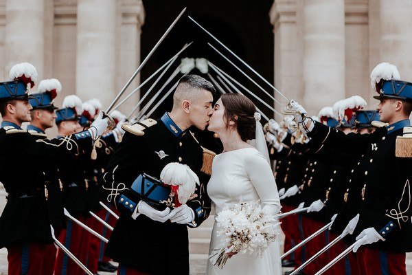 bride in retro wedding dress kisses groom in full military attire at the end of a saber arch