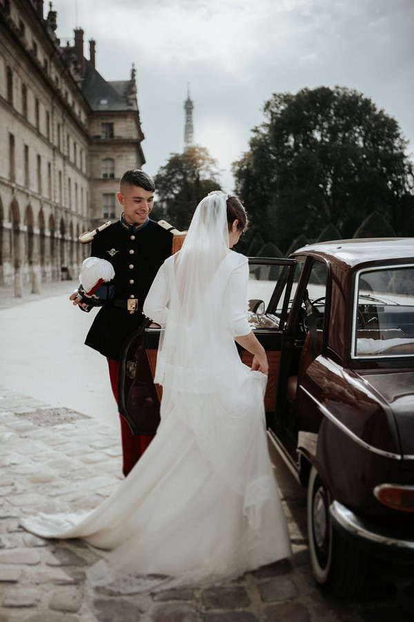 Groom holds door to red vintage car open for his bride