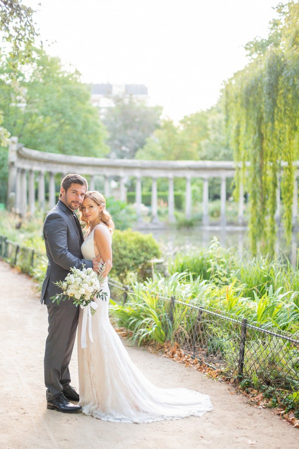 Husband and wife pose in front of lake inside Parc Monceau
