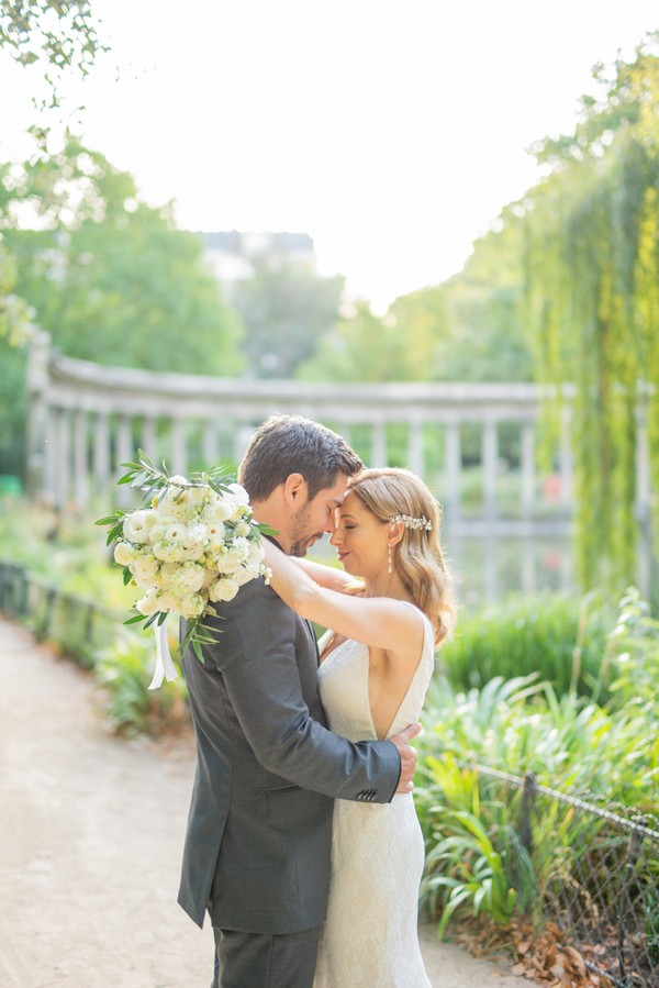 Bride and groom embrace surrounded by lush green gardens