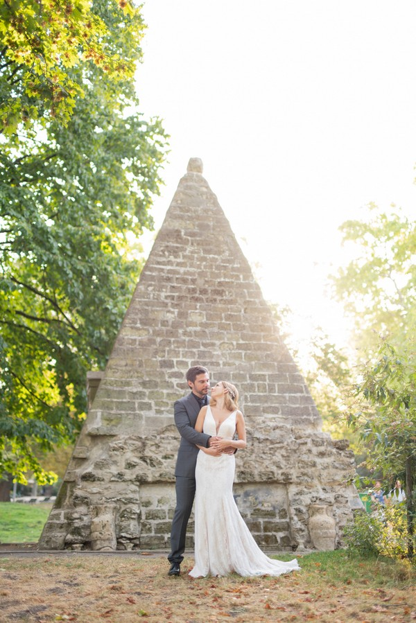 Bride and groom pose in front of miniature egyptian pyramid in Parc Monceau in Paris