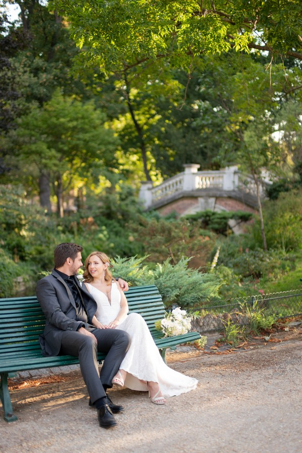 Bride and groom seated on green park bench