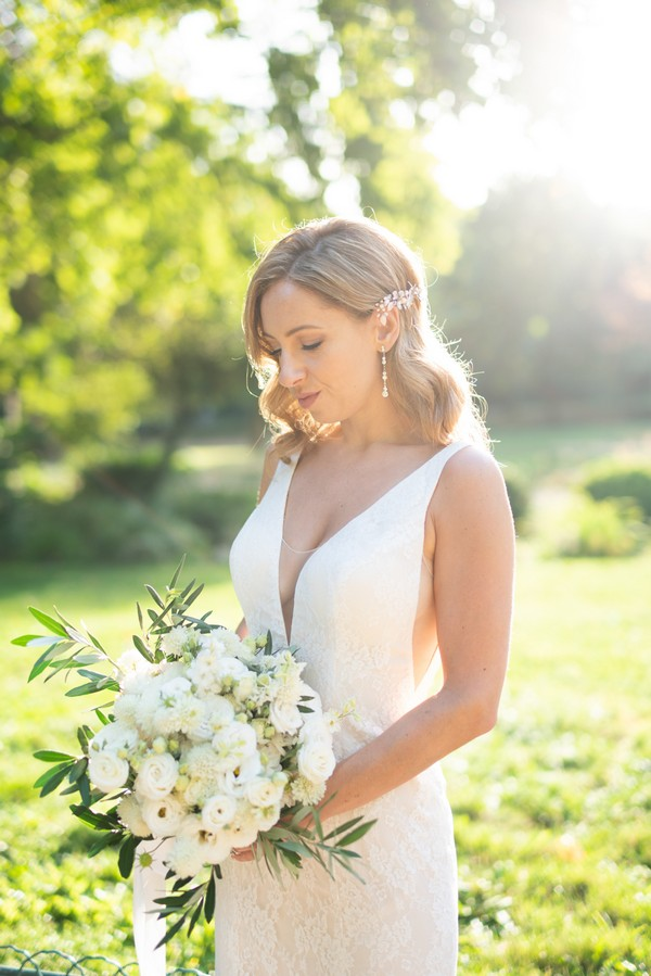 Bride holding white bouquet framed by green trees and sunlight