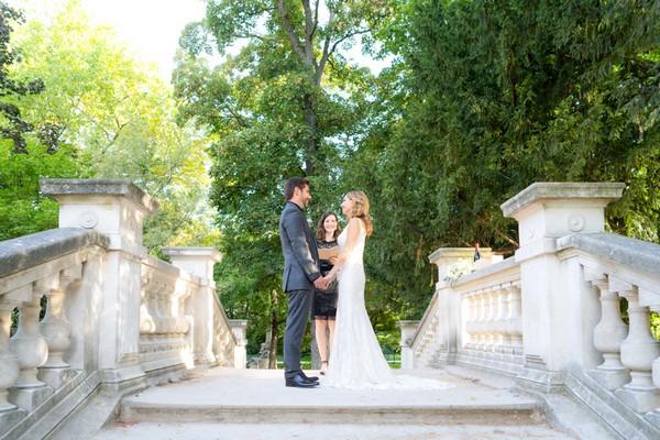 Couple stand on stone bridge for Romantic Ceremony in Parc Monceau Paris