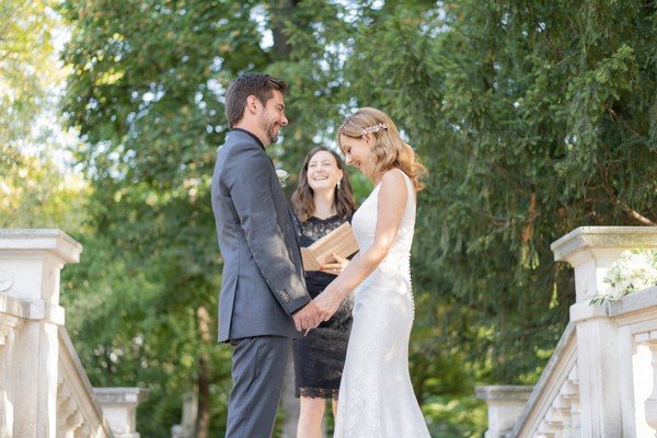 Bride smiles broadly while taking her husband hands in front of officiant
