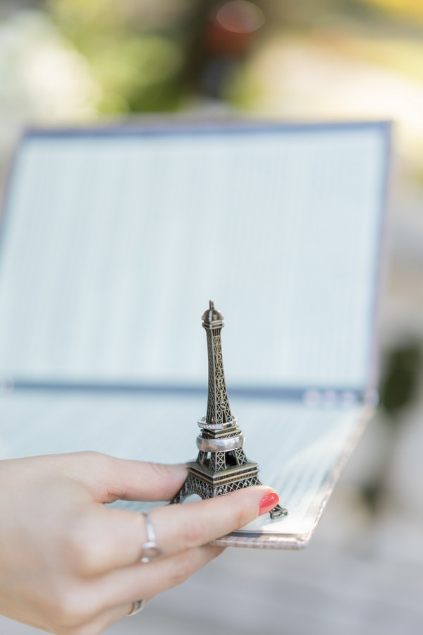 Wedding Celebrant holds book and mini eiffel tower statue