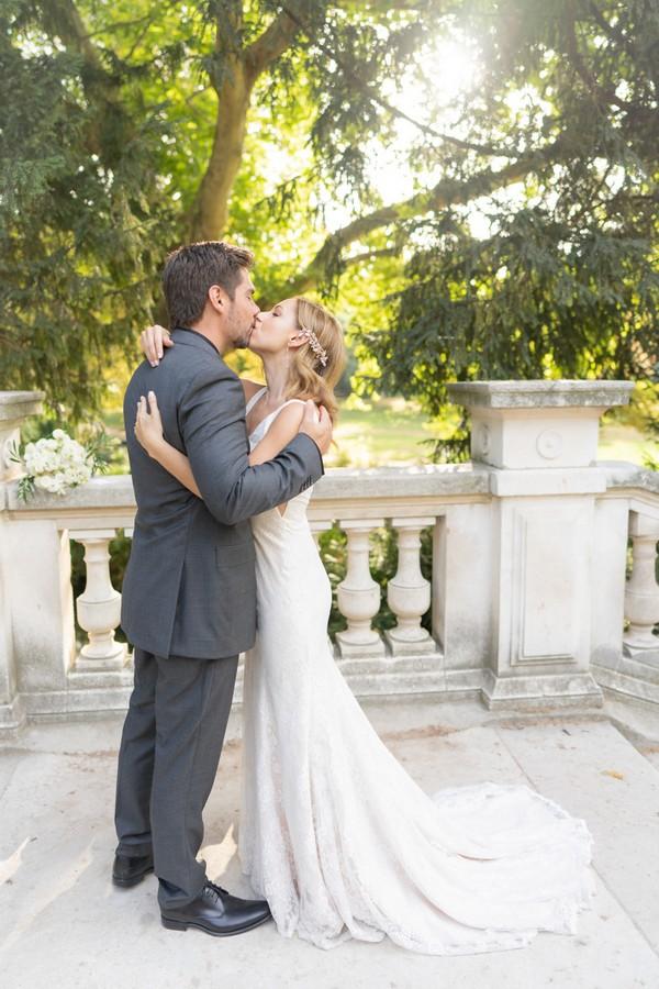 bride and groom kiss on stone bridge in Parc Monceau, Paris