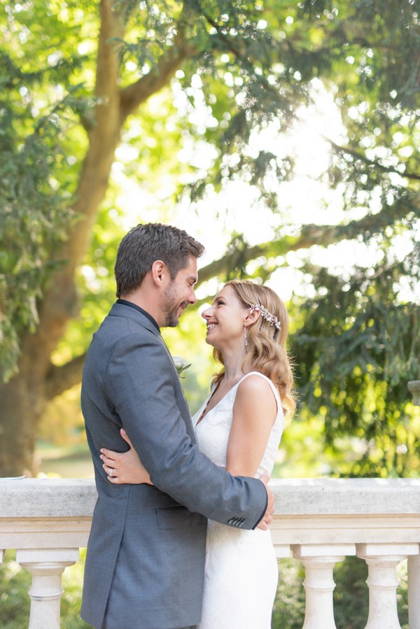 Bride and groom smile at the end of their romantic ceremony on stone bridge in Parc Monceau, Paris