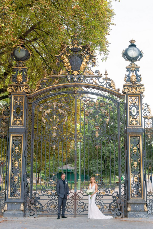 bride and groom stand in front of black and gold wrought iron gates