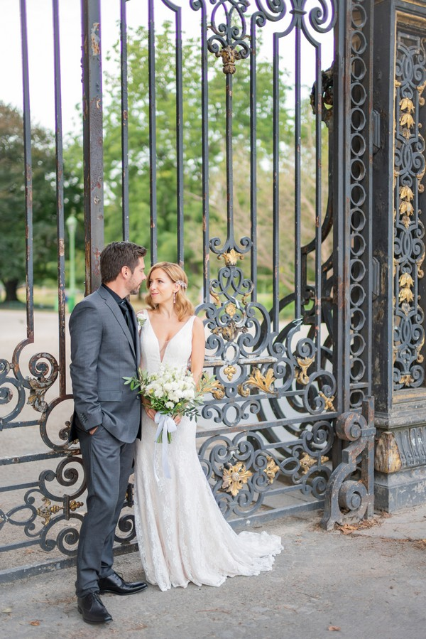 bride and groom look at each other in front of wrought iron gates
