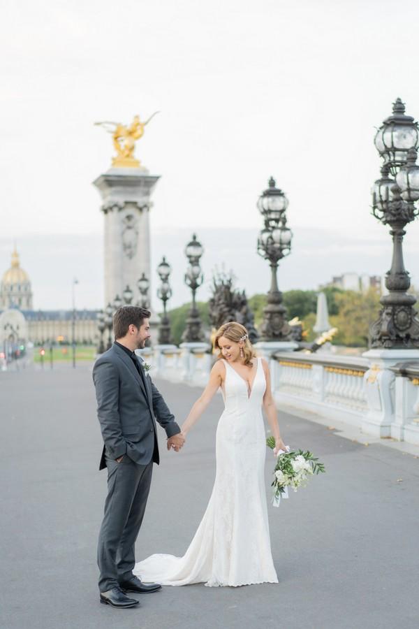 bride and groom walk across Alexander III bridge in Paris