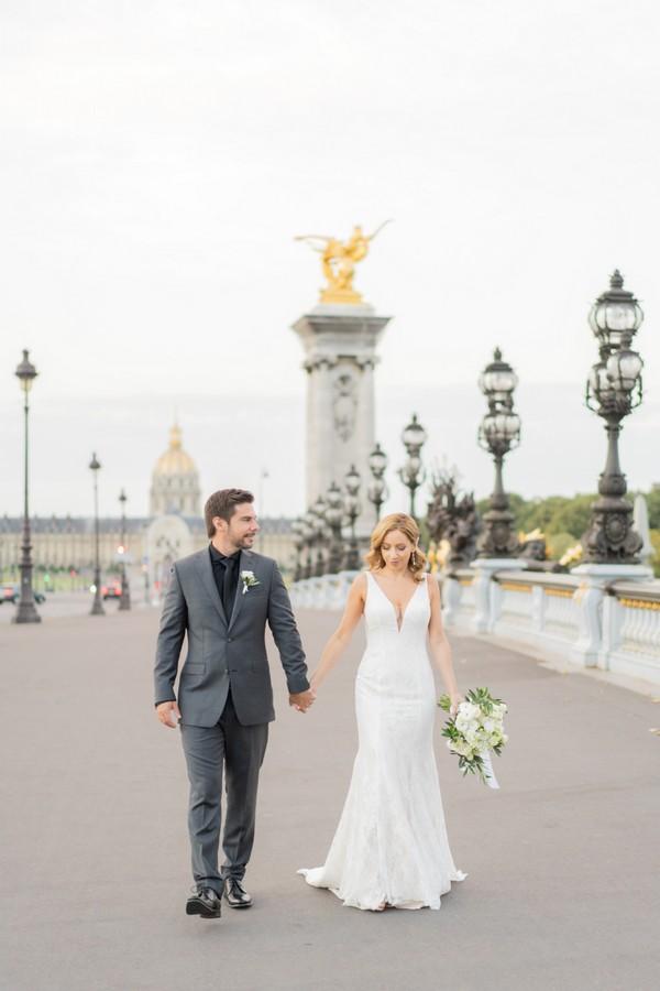 bride and groom walking on Alexander III bridge in Paris
