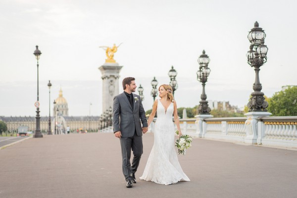 Bride and groom walking amongst lanterns of Alexander III bridge in Paris