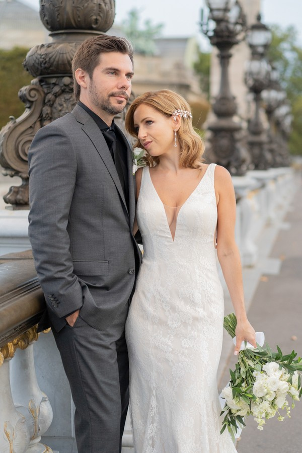 bride and groom pose on Alexander III bridge in Paris
