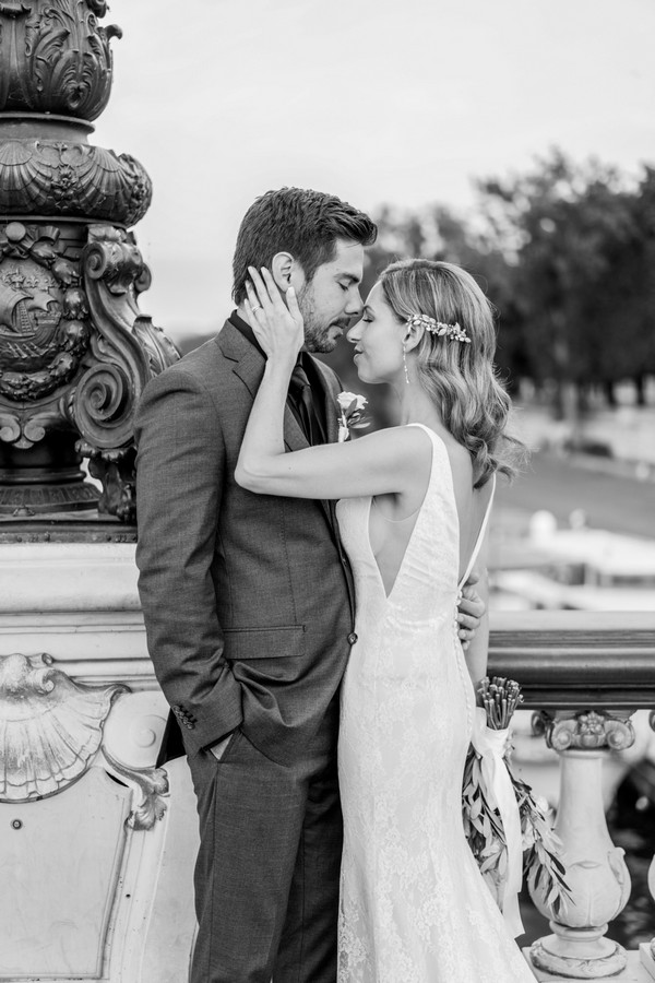 black and white image of bride holding grooms neck both with their eyes closed