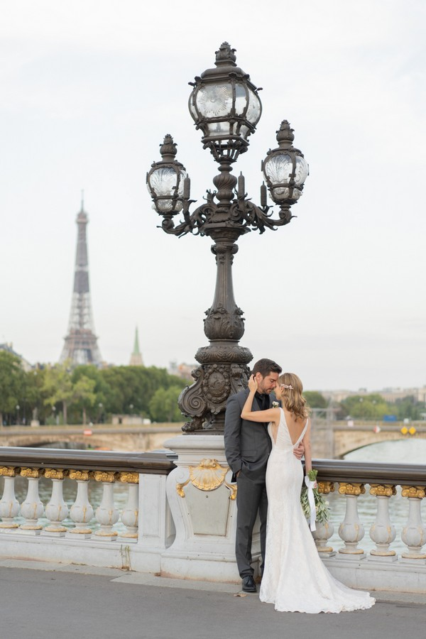 bride and groom close eyes and kiss in front of view of the Eiffel Tower