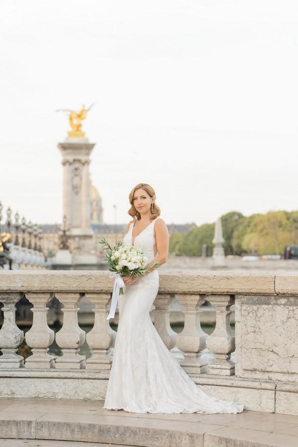 bride poses alone with bouquet on Alexander III bridge