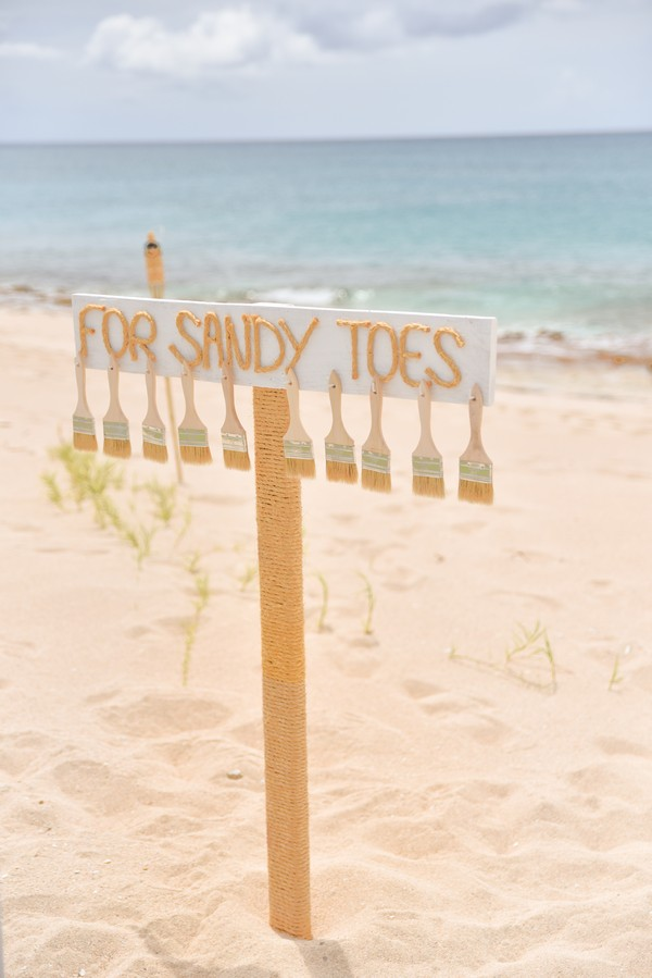 """paint brushes hang on sign in sand that says """"For Sandy Toes"""""""