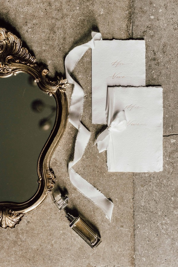 Flat lay of mirror and wedding stationery with rustic torn ribbon