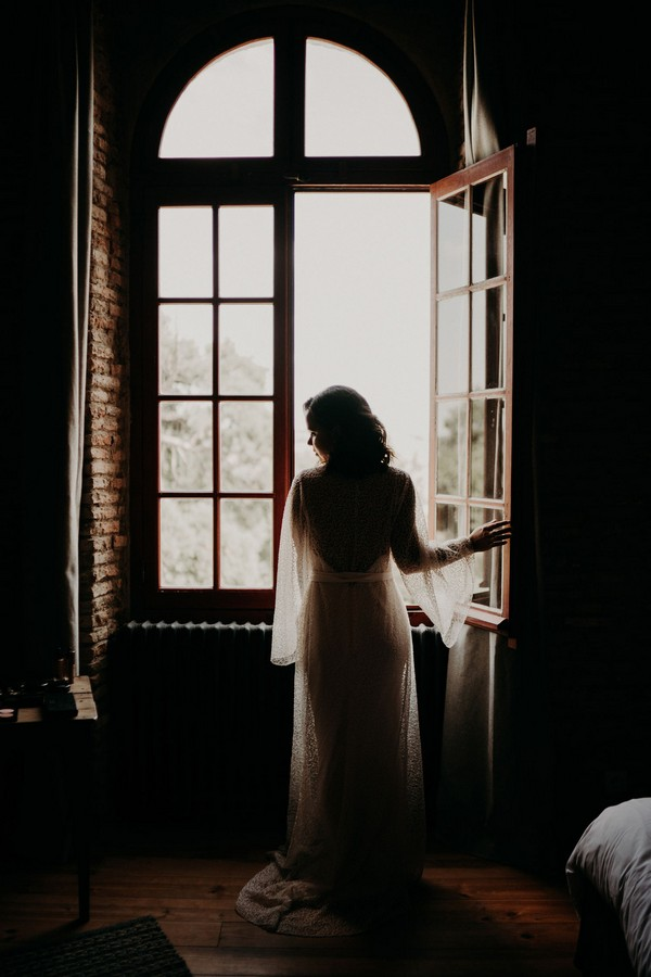 Silhouette of bride in arched window Chateau de Fajac for modern cultural affair