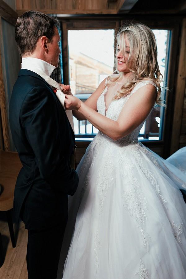 Bride ties grooms bow tie