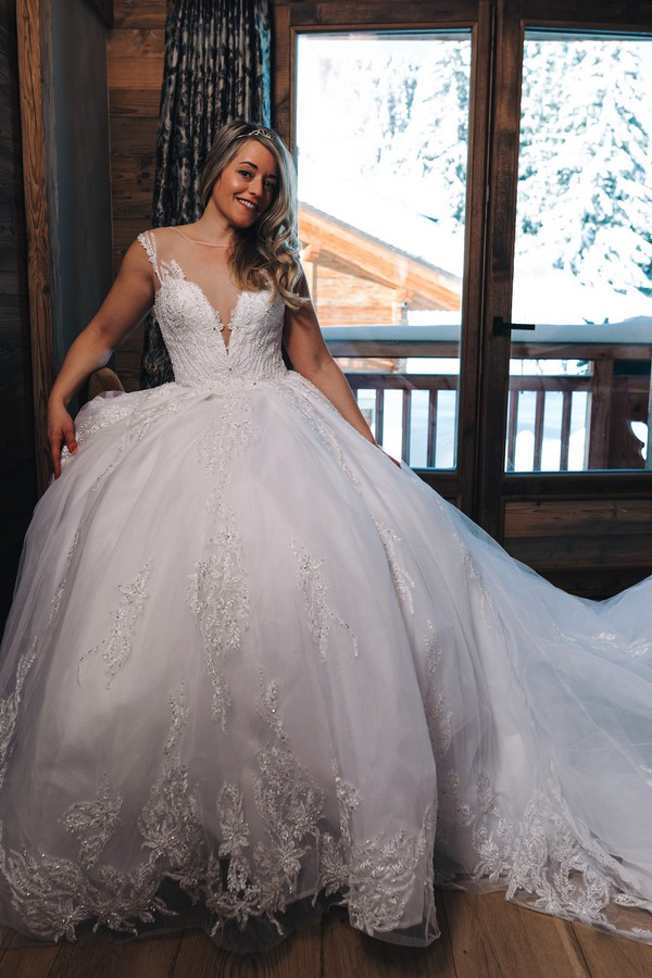 bride poses in white large skirted wedding gown with crystal beading