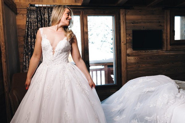 bride looks over her shoulder and smiles, her wedding dress trails behind her