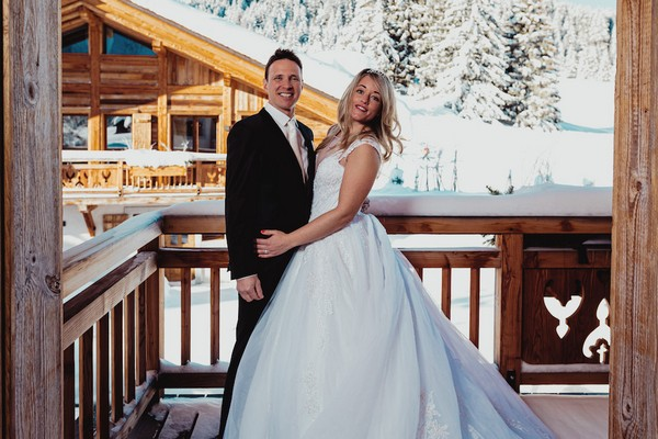 bride and groom posing on the balcony of a private chalet in french alps with snow and trees visible in the background