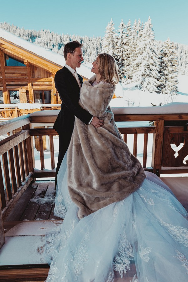 bride wrapped in a fur blanket and groom in black suit with snow and trees behind them
