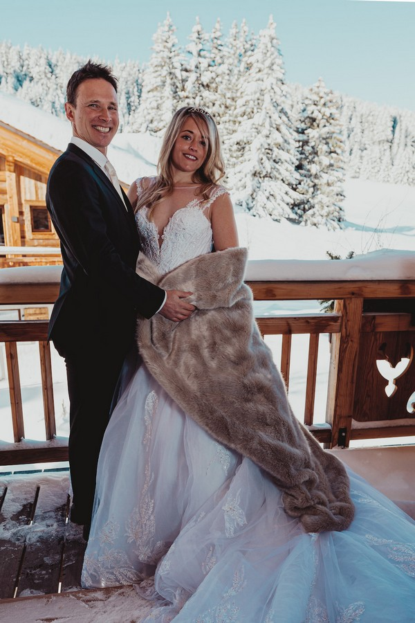 bride and groom smile at camera they stand on the balcony of a wooden chalet in the snowy french alps