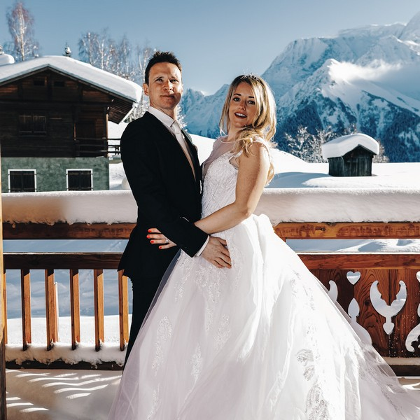 bride and groom in front of snowy backdrop of mountains, trees and chalets