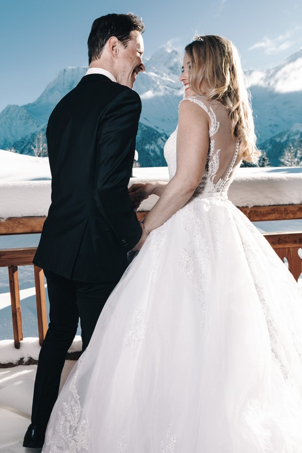 bride and groom laugh and turn back to camera, a snowy mountain is visible in the backfground