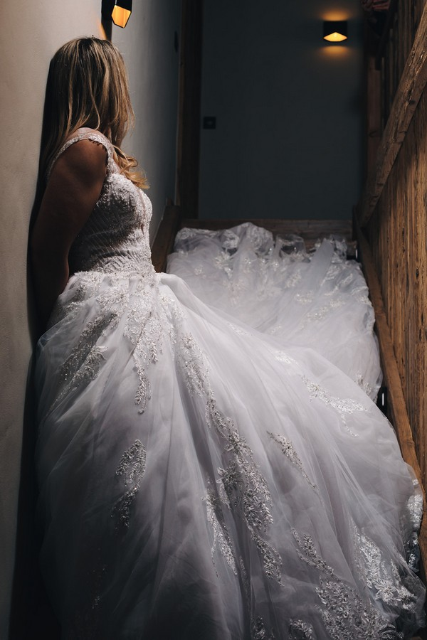 bride stands in a shadowy stair well and her dress trails up the stairs behind her, she is turned away from the camera